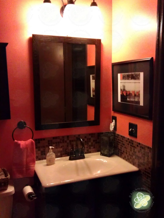 AFTER:  The mirror, picture (is a print from The Gates, which the orange matches) and another candle holder on the sink.