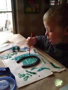 Booga painting a horseshoe.